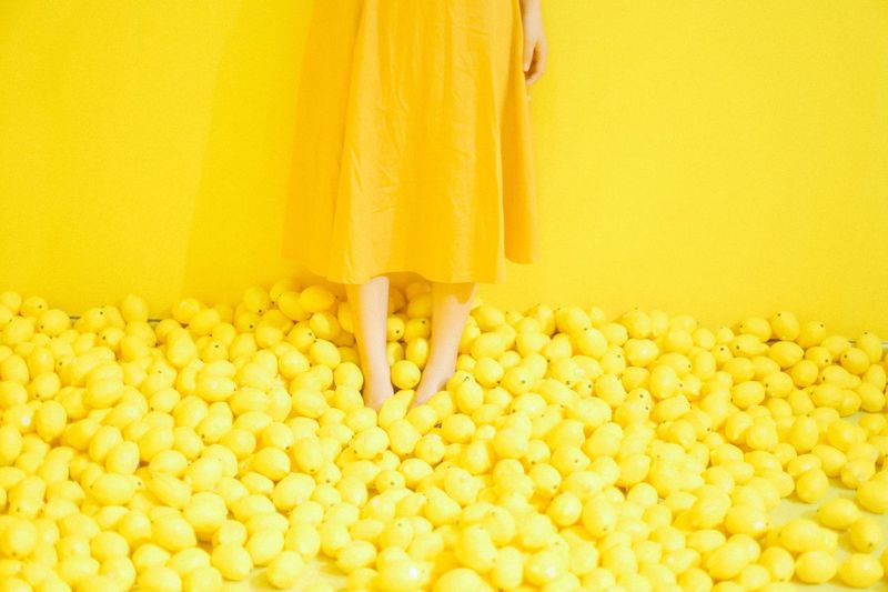 Midsection Of Woman Standing On Lemons Against Wall