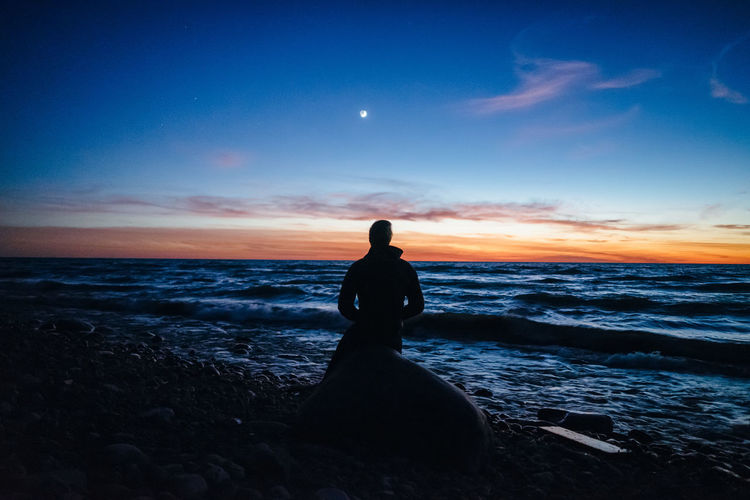 Man sitting on rock at beach against sky during sunset