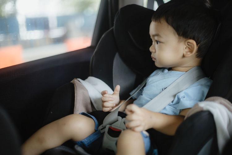 Asian boy sitting in car seat