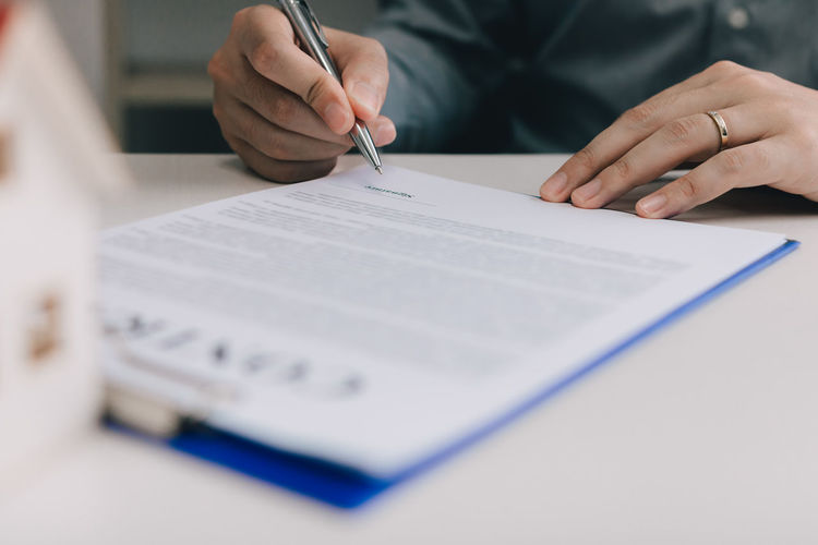Pen Table Writing Human Hand Holding Paper Signing Real Estate Contract Signature Buyer Document Business Mortgage Home House Property Ownership Landlord Loan  Insurance Agent RENT Lawyer