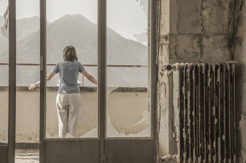Rear view of woman seen through broken door