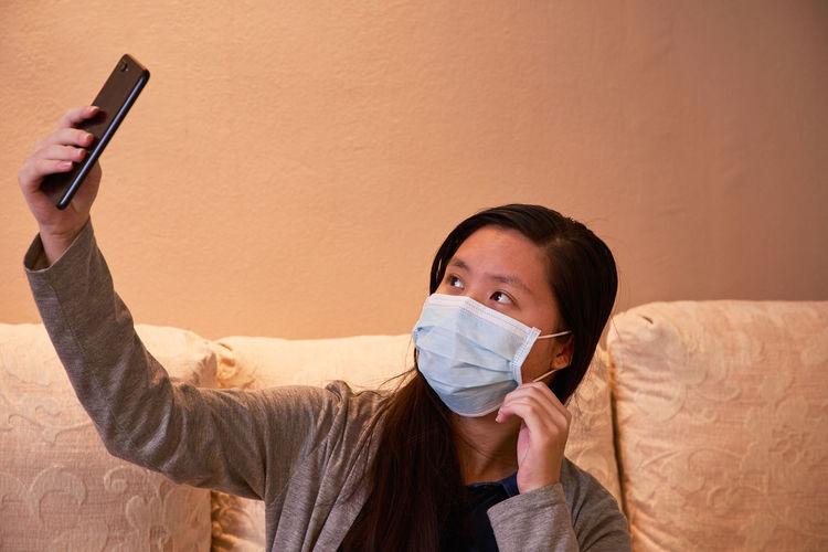 Close-up of girl wearing mask taking selfie at home