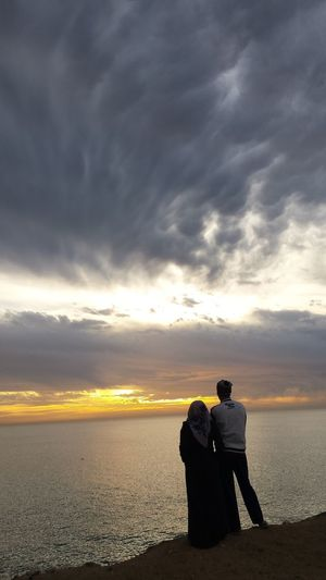 A couple standing on beach against sky during sunset
