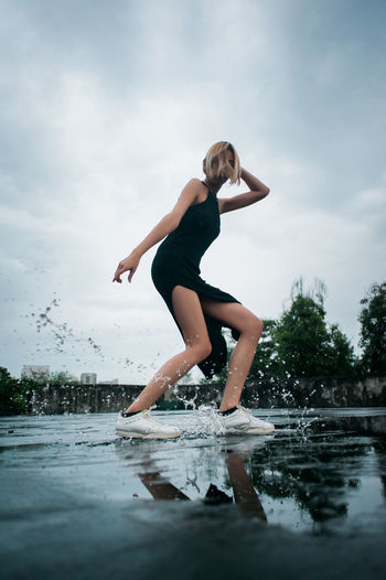 Full Length Of Young Woman Jumping In Puddle Against Sky
