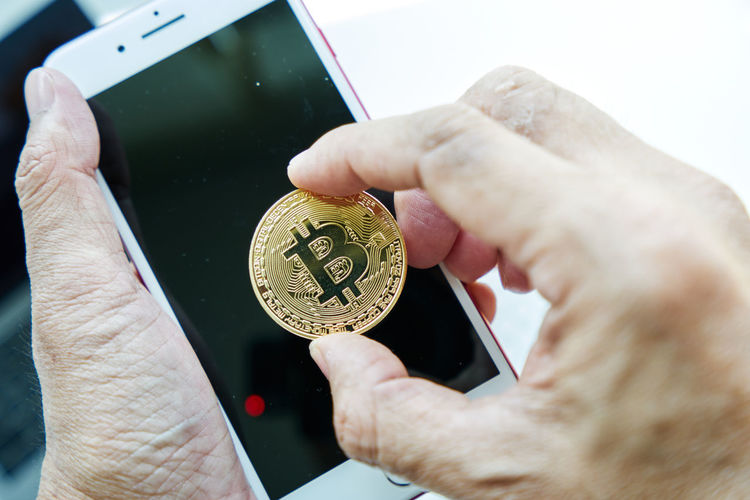 Man hand holding the gold Bitcoins and smartphone. Crypto Currency Money Digital Bitcoins Close-up Crypto Currency Cryptography Currency Digital Money Holding Human Hand Smartphone
