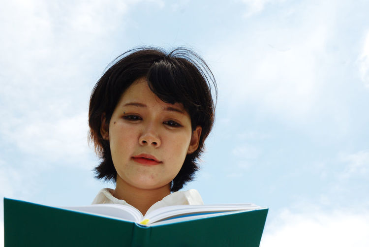 Low angle view of woman reading diary against sky