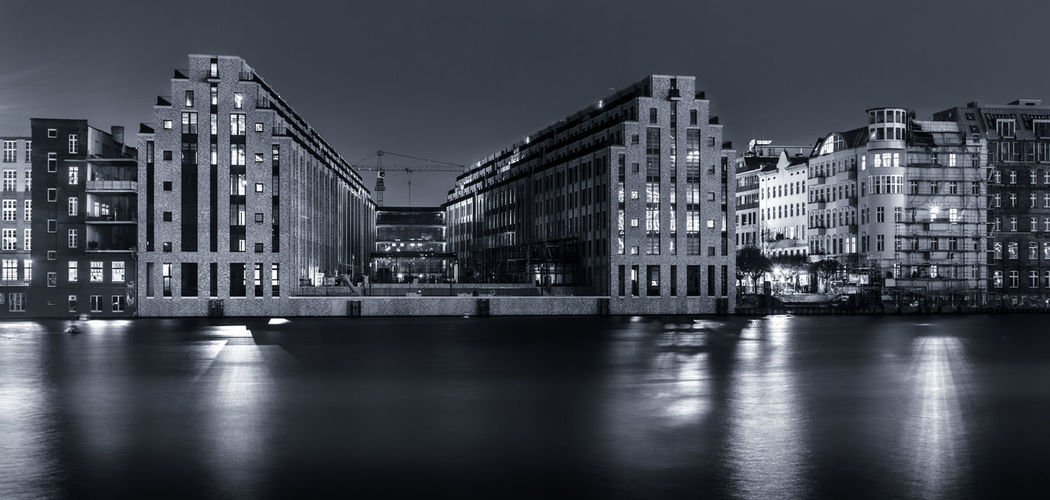 Illuminated buildings by river against sky at dusk