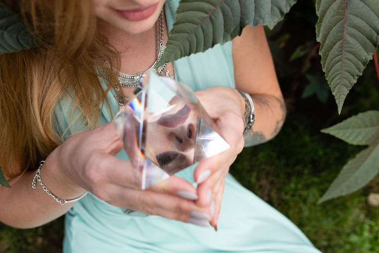 Midsection of woman holding crystal pyramid