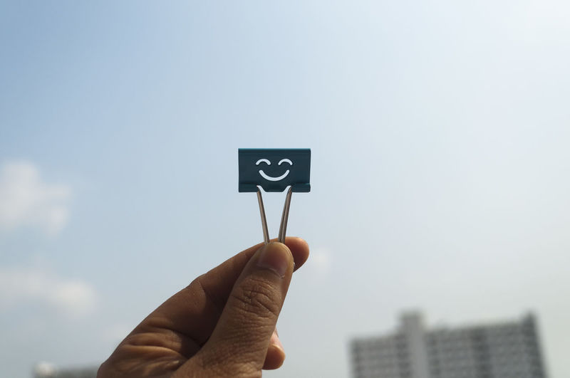 Cropped Hand Holding Smiley Paper Clip Against Sky