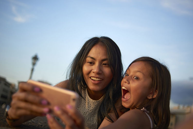 Portrait of smiling woman using smart phone against sky