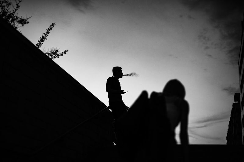 Low angle view of silhouette man smoking while standing against sky