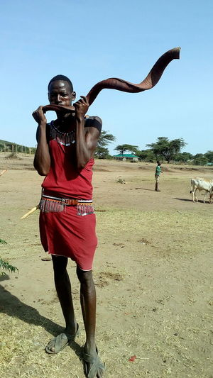 Mara Tri Celebration Instrument Clear Sky Day Front View Full Length Leisure Activity Lifestyles Looking At Camera Made From Antler's Horn Mammal Men Musical Hor Nature One Person Outdoors People Portrait Real People Sand Sky Standing Young Adult