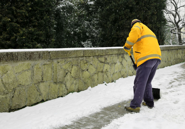Side view of man removing snow with shovel on footpath against trees