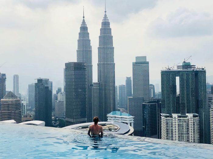 Woman swimming in infinity pool against modern buildings in city