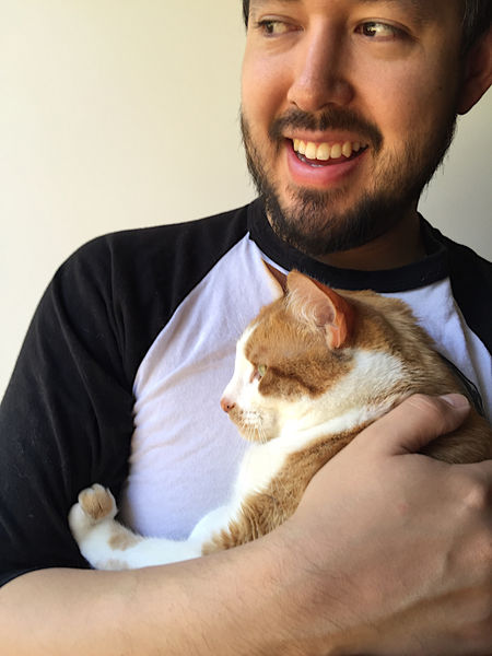 Man with his cat Arm Bearded Calm Casual Clothing Cat Contented Feline Ginger Tabby Hand Happy Holding Indoors  Mammal Man Natural Light One Animal One Person Orange And White Cat Pets Relaxation Smiling