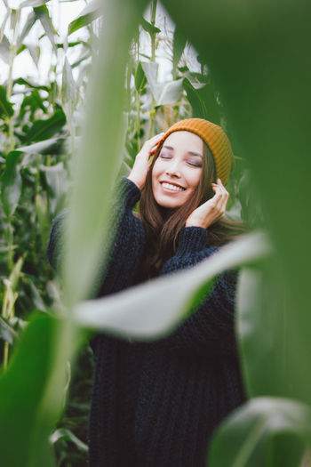 Young woman with eyes closed amidst plants