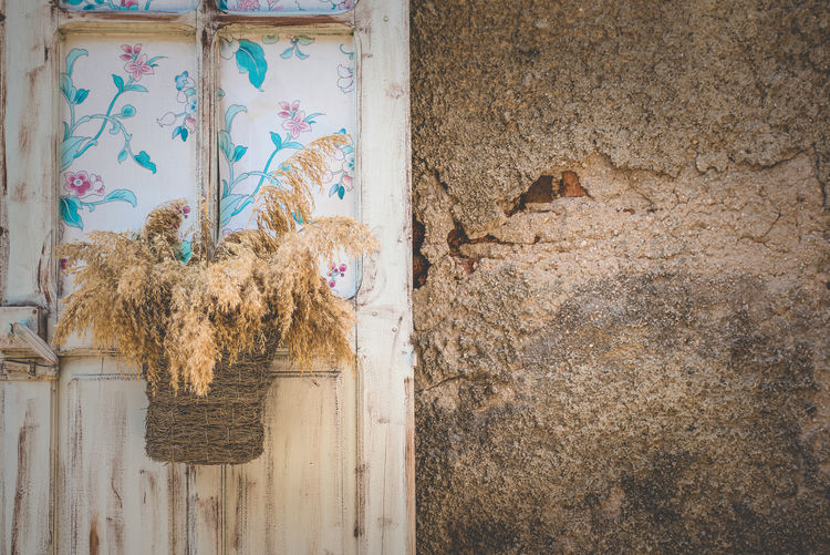 Rustic Charm by Anna Wacker Wall - Building Feature Old Day Weathered No People Built Structure Architecture Damaged Abandoned Indoors  Wall Entrance Decline Run-down Obsolete Art And Craft Door Deterioration Floral Pattern Old Doors, Weathered White, Weathered Brown Edge, Antique Doors Still Life Faded Beauty Rustic Scene Shabby Chic Romantic