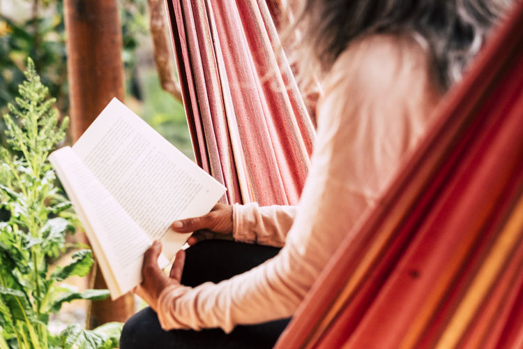 Midsection of woman reading book while sitting on hammock