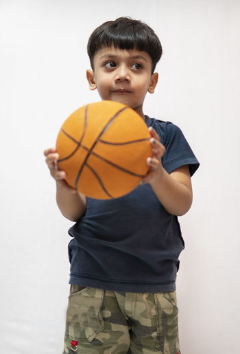 Boy holding ball while standing against white background