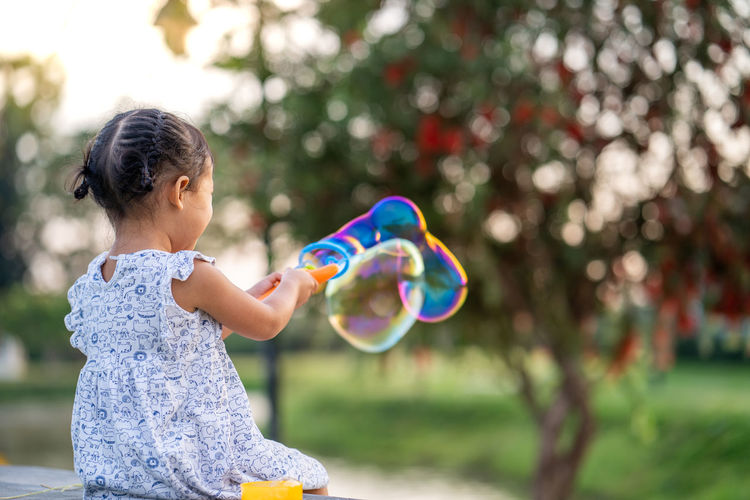 Cute little girl playing with soap bubbles at park.