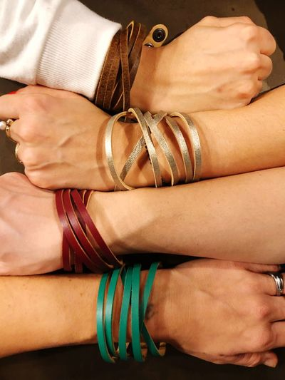 Cropped hands of people wearing colorful bracelets