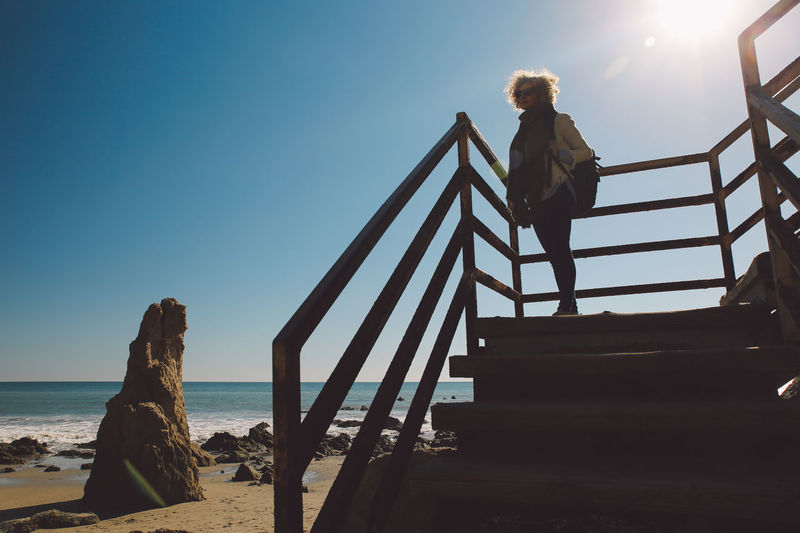 Woman standing on stairs at beach against sky