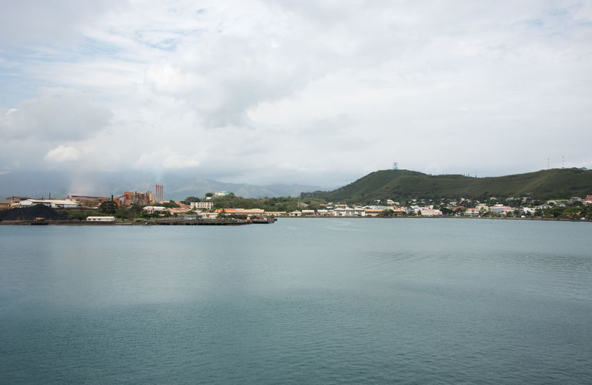 Noumea, New Caledonia-November 25,2016: Noumea waterfront, SLN plant and Pacific Ocean in New Caledonia. Industrial Industry Noumea Plant SLN Smoke Stack South Pacific Architecture Building Exterior Built Structure City Cityscape Cloud - Sky Environmental Issues Island Mountain Nature New Caledonia Nickel Outdoors Pacific Ocean Pollution Sea Water Waterfront