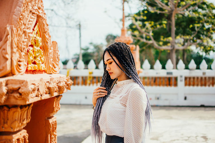 Side view of young woman standing outdoors
