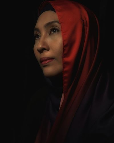 Close-up of thoughtful woman against black background