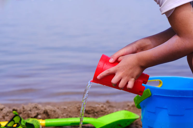 Close-up of hand holding toy against sea