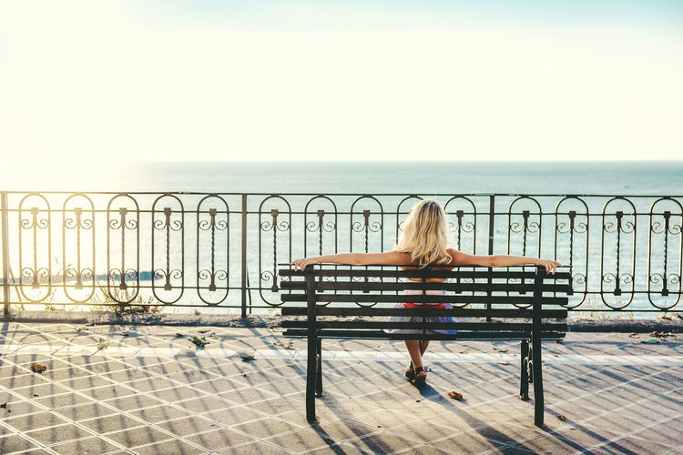 Blond woman sitting on a bench and looking at sea Bench Blonde Coastline Holidays Mediterranean Sea Naples Pedestrian Walkway Relaxing Sitting Vacations Woman Beauty In Nature Coast Enjoy Horizon Over Water Italy One Person Only Women Outdoors Scenery Scenics Sea Sky Sorrento Sun
