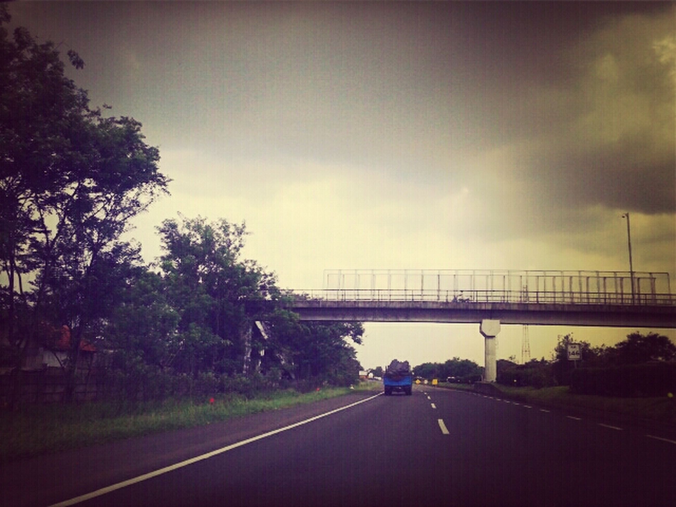 transportation, road, the way forward, car, road marking, sky, land vehicle, mode of transport, diminishing perspective, connection, tree, on the move, cloud - sky, vanishing point, bridge - man made structure, street, highway, cloudy, street light, travel