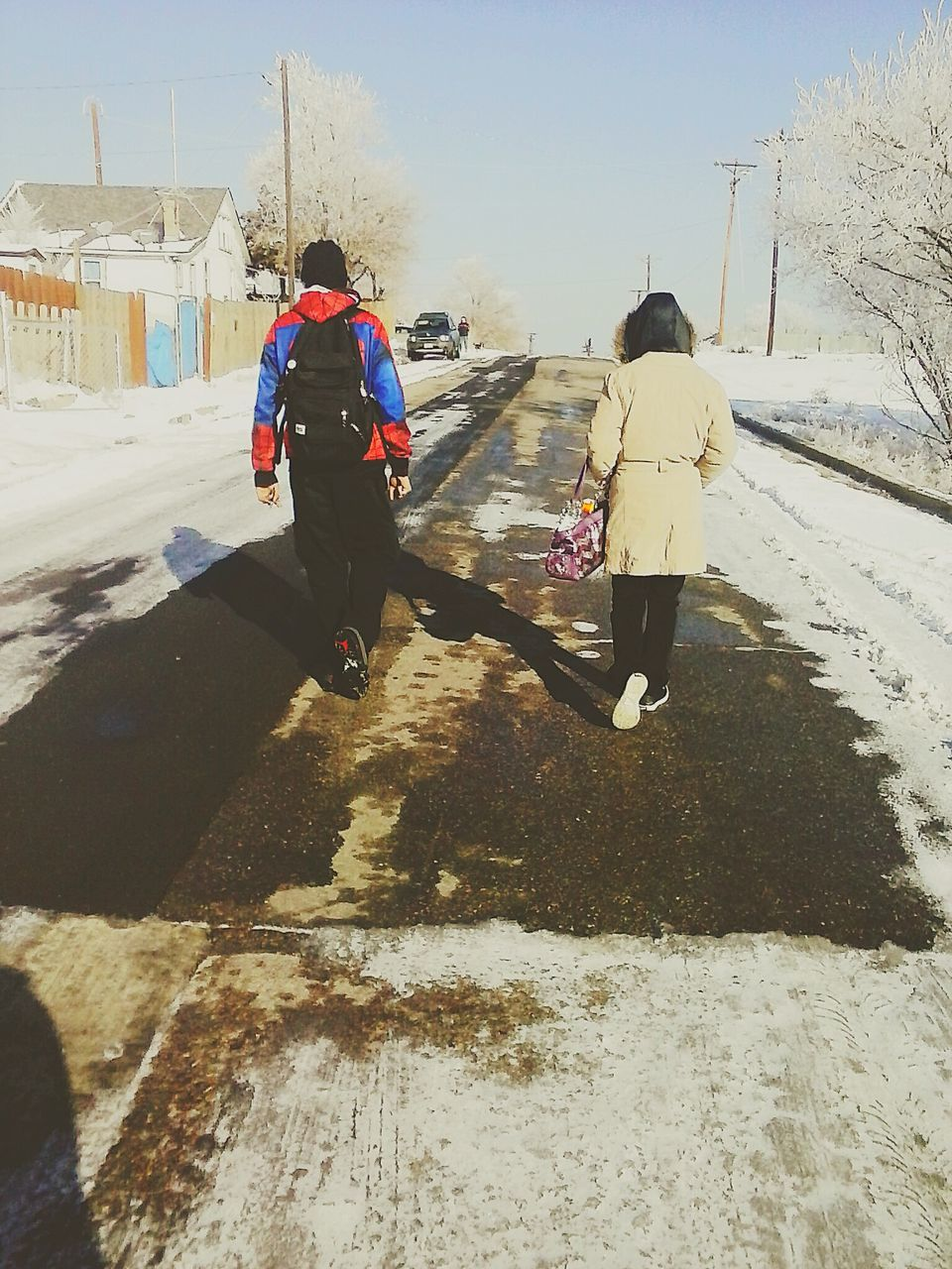 rear view, real people, winter, full length, walking, snow, cold temperature, leisure activity, women, day, lifestyles, two people, sunlight, outdoors, men, shadow, warm clothing, architecture, building exterior, nature, sky, people