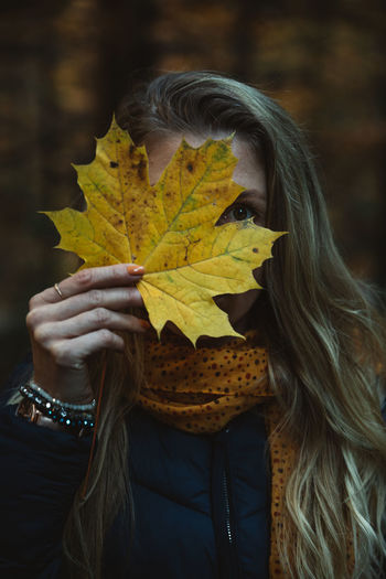 Portrait of woman holding maple leaves during autumn