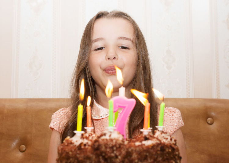 Cute girl blowing birthday candles on cake at home