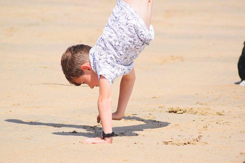 Boy In Handstand On Beach