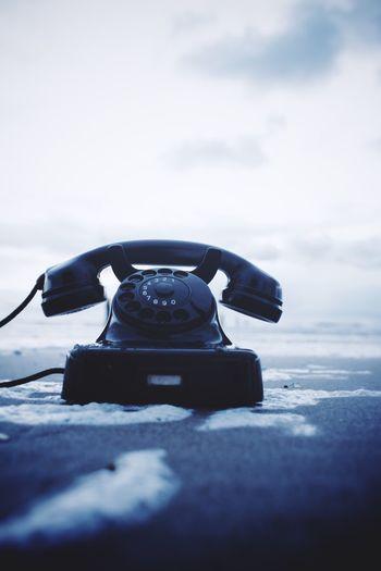 Rotary Phone On Beach Against Sky
