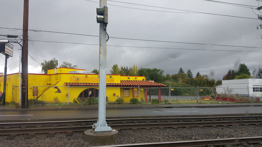 Closed businesses in Rockwood. Bright colors under ominous skies along the Max line. Yellow Transportation Rain No People The City Light Cloud - Sky Architecture Building Exterior Multi Colored Colors Of LifeLooking Through Window Weather Dramatic Sky Cityscape City Light