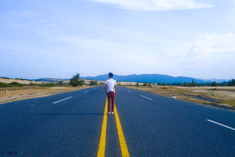 Rear view of man standing on country road against sky