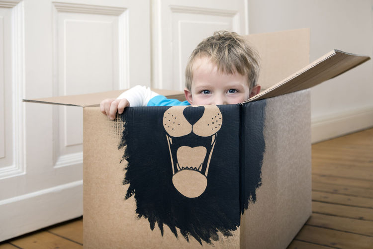 Portrait of cute boy in box at home