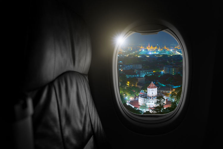 Airplane interior with window view of grand palace bangkok, thailand, travel and air transportation.