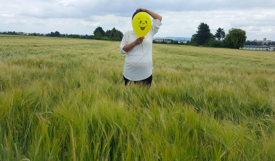 Person holding balloon with smiley over face while standing on field