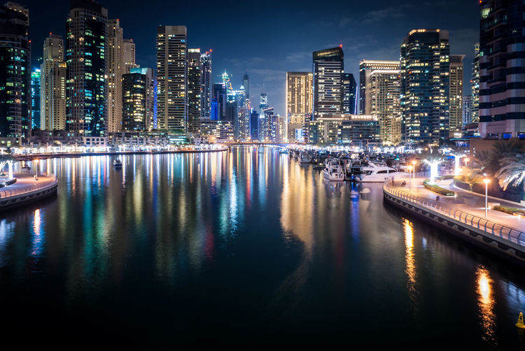 Illuminated dubai marina with reflection in marina at night