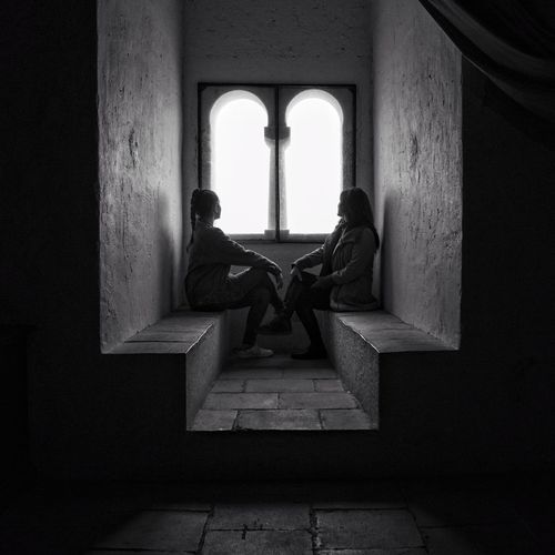 Side view of mother and daughter sitting on seats by window