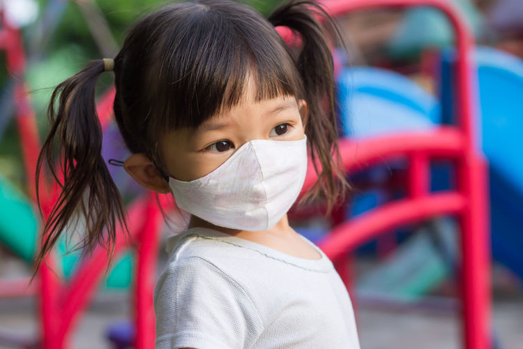 cute girl wearing mask looking away while standing outdoors