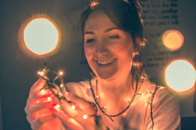 Smiling Woman Holding Illuminated Lights In Darkroom