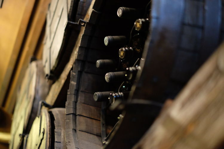 Low angle view of wine bottles in barrels at cellar