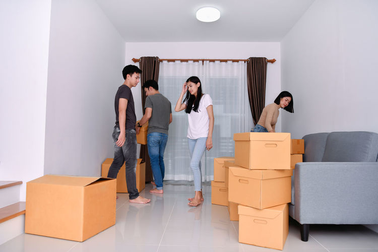 Adult Box Box - Container Cardboard Cardboard Box Casual Clothing Front View Full Length Group Of People Indoors  Lifestyles Moving House People Real People Standing Togetherness Women Young Adult Young Men Young Women