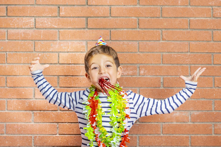Portrait of excited boy wearing party equipment against brick wall