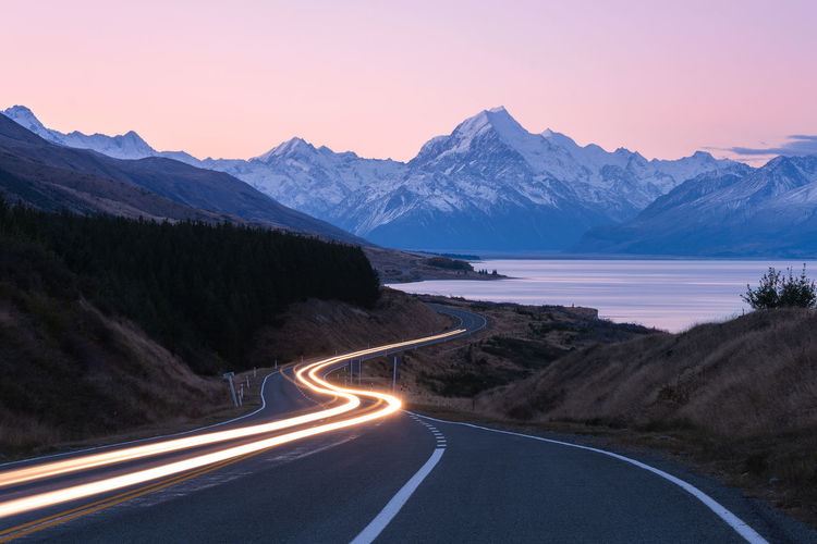 Light Trails On Road By Mountains Against Sky During Sunset